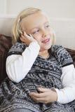 Ragazza che per mezzo del telefono cellulare sul sofà Fotografia Stock