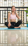 Ragazza che per mezzo del telefono su una stuoia di yoga a casa Immagini Stock Libere da Diritti