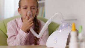 Ragazza che per mezzo dell'inalatore del nebulizzatore con la maschera video d archivio