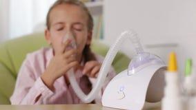 Ragazza che per mezzo dell'inalatore del nebulizzatore, sorridere alleviato stock footage