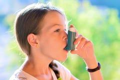 Ragazza che per mezzo dell'inalatore di asma immagine stock