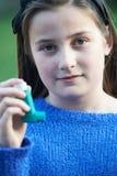 Ragazza che per mezzo dell'inalatore per trattare attacco di asma Fotografia Stock