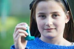Ragazza che per mezzo dell'inalatore per trattare attacco di asma Immagini Stock Libere da Diritti