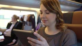 Ragazza che per mezzo della compressa, Internet serfing Passeggero in treno archivi video