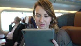 Ragazza che per mezzo della compressa, Internet serfing Passeggero in treno stock footage