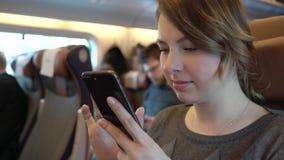 Ragazza che per mezzo dello smartphone, Internet serfing Passeggero in treno archivi video