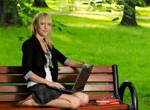 Ragazza che per mezzo di un computer portatile che studia per l'esame Fotografia Stock