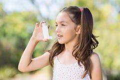 Ragazza che per mezzo di un inalatore di asma fotografia stock libera da diritti