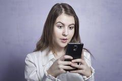 Ragazza che per mezzo di uno smartphone Immagine Stock