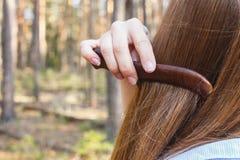 Ragazza che pettina capelli con un pettine di legno nella foresta fotografia stock libera da diritti