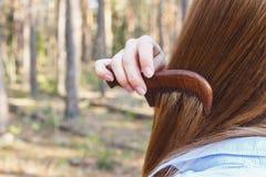 Ragazza che pettina capelli con un pettine di legno nella foresta fotografia stock
