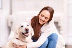 Ragazza che picchietta il suo cane di animale domestico fotografia stock libera da diritti