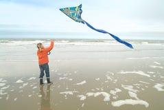 Ragazza che pilota un cervo volante alla linea costiera Fotografie Stock Libere da Diritti