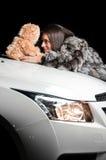 Ragazza che pone sul cappuccio dell'automobile con il giocattolo della peluche Fotografia Stock