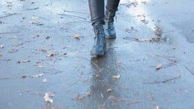 Ragazza che porta gli stivali di combattimento neri che spruzzano in una pozza dopo la pioggia stock footage