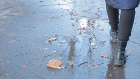 Ragazza che porta gli stivali di combattimento neri che spruzzano in una pozza dopo la pioggia archivi video