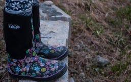Ragazza che porta gli stivali di gomma neri con le progettazioni rosa immagini stock libere da diritti