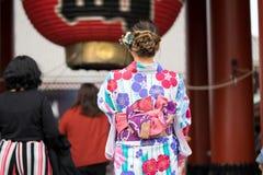 Ragazza che porta kimono giapponese che sta davanti al tempio di Sensoji a Tokyo, Giappone Il kimono ? un indumento tradizionale  fotografia stock