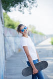 Ragazza che porta maglietta bianca in bianco, jeans che posano contro la parete ruvida della via Immagine Stock Libera da Diritti