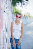 Ragazza che porta maglietta bianca in bianco, jeans che posano contro la parete ruvida della via Immagini Stock