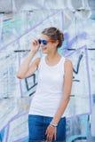 Ragazza che porta maglietta bianca in bianco, jeans che posano contro la parete ruvida della via Fotografia Stock Libera da Diritti