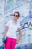Ragazza che porta maglietta bianca in bianco, jeans che posano contro la parete ruvida della via Immagine Stock
