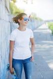 Ragazza che porta maglietta bianca in bianco, jeans che posano contro la parete ruvida della via Fotografia Stock