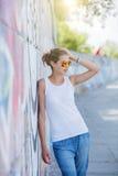 Ragazza che porta maglietta bianca in bianco, jeans che posano contro la parete ruvida della via Immagini Stock Libere da Diritti