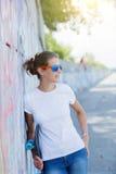 Ragazza che porta maglietta bianca in bianco, jeans che posano contro la parete ruvida della via Fotografie Stock Libere da Diritti