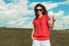 Ragazza che posa in natura con la mano in tasca mentre mostrando vittoria Fotografie Stock