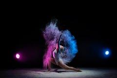 Ragazza che posa in nuvola di polvere di colore in studio Immagine Stock Libera da Diritti