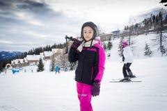 Ragazza che posa sopra il pendio dello sci con l'attrezzatura dello sci Immagini Stock