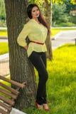 Ragazza che posa in un parco vicino ad un albero fotografie stock