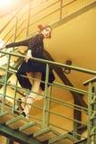 Ragazza che posa in vestito alla moda e nero sulle scale metalliche immagini stock