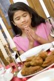 Ragazza che prega durante il pranzo Fotografie Stock Libere da Diritti