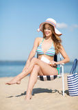 Ragazza che prende il sole sulla sedia di spiaggia Fotografia Stock