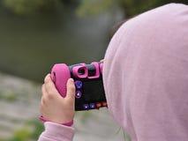 Ragazza che prende immagine con la macchina fotografica del ` s dei bambini Fotografia Stock