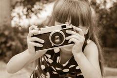 Ragazza che prende le fotografie con la macchina fotografica d'annata Immagine Stock