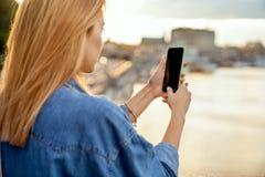 Ragazza che prende le immagini di un paesaggio, primo piano di un telefono in lei immagini stock