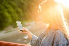 Ragazza che prende le immagini di un paesaggio, primo piano di un telefono in lei immagine stock libera da diritti