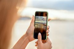 Ragazza che prende le immagini di un paesaggio, primo piano di un telefono in lei immagine stock