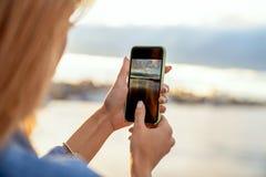 Ragazza che prende le immagini di un paesaggio, primo piano di un telefono in lei fotografie stock libere da diritti
