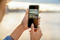 Ragazza che prende le immagini di un paesaggio, primo piano di un telefono in lei fotografia stock