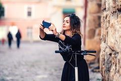Ragazza che prende selfie con la macchina fotografica mentre guidando un motorino di scossa fotografia stock