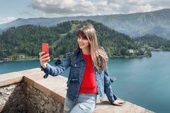 Ragazza che prende selfie dalla cima del castello della montagna con la vista della valle e del lago sui precedenti Fotografia Stock Libera da Diritti