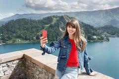 Ragazza che prende selfie dalla cima del castello della montagna con la vista della valle e del lago sui precedenti Esaminando la Fotografia Stock