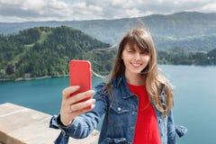 Ragazza che prende selfie dalla cima del castello della montagna con la vista della valle e del lago sui precedenti Esaminando la Immagini Stock