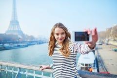 Ragazza che prende selfie vicino alla torre Eiffel Fotografia Stock