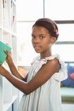 Ragazza che prende un libro dallo scaffale per libri in biblioteca Fotografia Stock