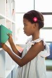 Ragazza che prende un libro dallo scaffale per libri in biblioteca Fotografia Stock Libera da Diritti